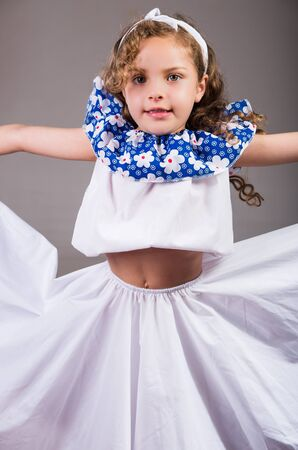 dance preteen: Cute little girl wearing beautiful white and blue dress with matching head band, actively posing for camera, studio background. Stock Photo