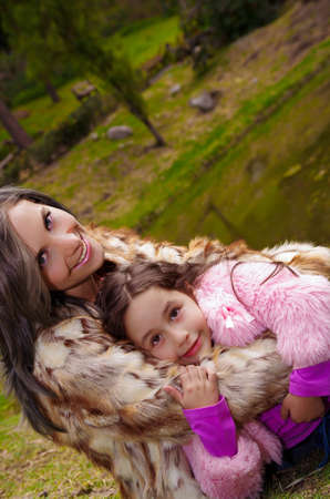 Mother with daughter both wearing fur clothing sitting outdoors embracing and smiling, green nature background.