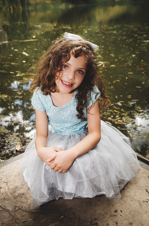 Cute little girl wearing beautiful blue dress with matching head band, posing for camera, outdoors lake background. Stock Photo
