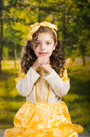 dance preteen: Cute little girl wearing beautiful yellow dress with matching head band, posing for camera, green forest background.