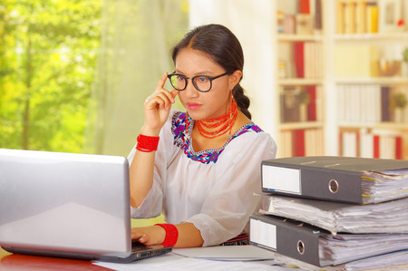 Young pretty girl wearing traditional andean clothing and glasses, sitting working by office desk with laptop computer, staring at screen, ring binders stacked on table, garden window background.