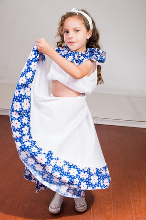 Cute little girl wearing beautiful white and blue dress with matching head band, actively posing for camera, studio background. Stock Photo