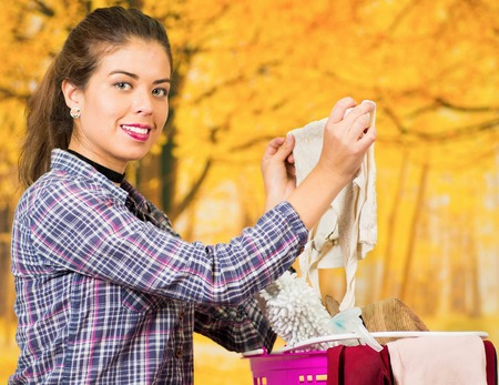 Attractive brunette wearing casual clothes sitting down, emptying pink plastic basket with different products, seen from profile angle, autumn forest background.