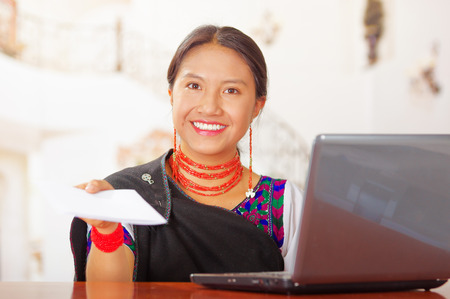 hotel receptionist: Young brunette wearing traditional native clothes working as hotel receptionist with friendly smile handing over papers to client across desk, customers point of view. Stock Photo