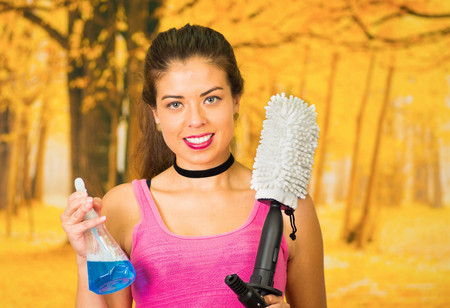 Attractive brunette wearing pink top posing while holding up cleaning product bottle and mop device which connects to water hose, autumn forest background.