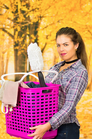 Attractive brunette wearing casual clothes while holding pink plastic basket with different products looking to camera, autumn forest background.