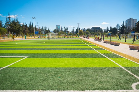 inner city: QUITO, ECUADOR - 8 AUGUST, 2016: Football fields located in inner city park La Carolina, artificial green grass surface, buildings visible background, beautiful sunny day.