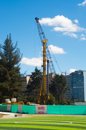 artifical: QUITO, ECUADOR - 8 AUGUST, 2016: Green artifical footbal fields located in inner city park La Carolina, with large construction crane in background, beautiful sunny day.