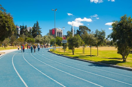 inner city: QUITO, ECUADOR - 8 AUGUST, 2016: Blue colored athletic running track located in inner city park La Carolina, people walking approaching camera, beautiful sunny day. Editorial