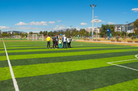 inner city: QUITO, ECUADOR - 8 AUGUST, 2016: Group of people standing on football field located in inner city park La Carolina, artificial green grass surface, buildings visible background, beautiful sunny day. Editorial
