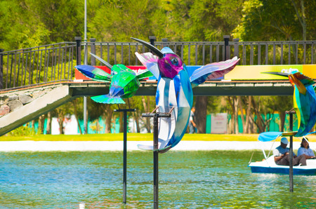 ruiseñor: Colorful mockingbird art installation placed on poles inside water laguna, sorrounded by trees, beautiful sunny day. Foto de archivo