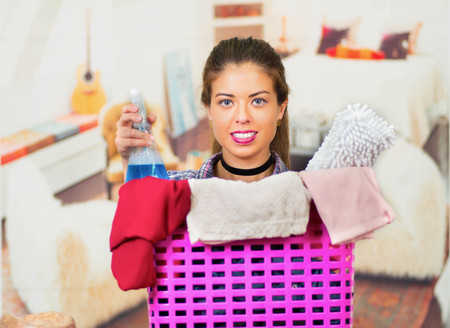 containing: Attractive brunette peeking out head from behind pink plastic laundry basket, holding spray bottle containing blue cleaning liquid, smiling and posing for camera, messy apartment background.