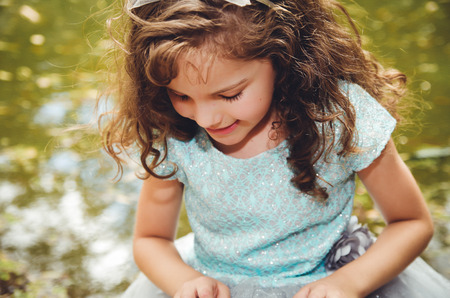 dance preteen: Cute little girl wearing beautiful blue dress with matching head band, posing for camera, outdoors lake background. Stock Photo