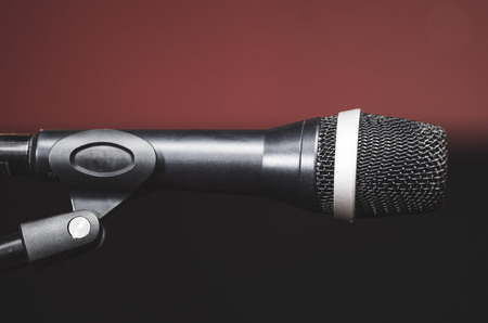 Closeup black vocal microphone mounted on mic stand, blurry red dark bcakground. Stock Photo