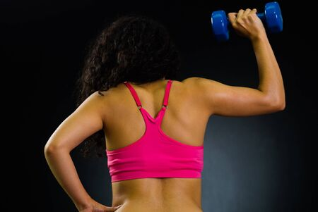 facing right: Athletic brunette woman wearing pink top, training lifting weights with right arm, back facing camera, black studio background.