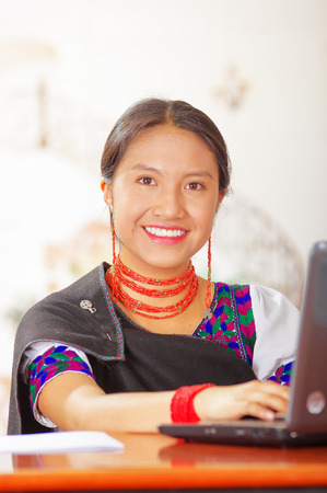 Young brunette wearing traditional native clothes working as hotel receptionist with friendly smile, using computer, customers point of view. Stock Photo