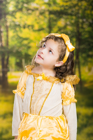 Cute little girl wearing beautiful yellow dress with matching head band, posing for camera, green forest background.