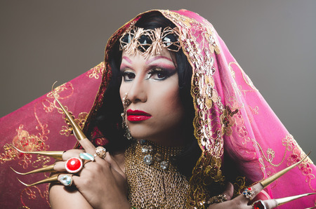 Headshot woman dressed in traditional hindu clothing, heavily decorated in gold and elegant veil, extremely long fingernails, posing artistically for camera, hindusim dancer concept.