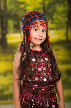 dance preteen: Cute little girl wearing beautiful red dress with matching pearl hat, posing for camera, green forest background. Stock Photo