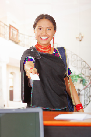 hotel receptionist: Young brunette wearing traditional native clothes working as hotel receptionist with friendly smile, processing payment using credit card terminal, customers point of view.