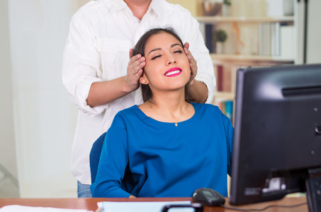 stress relief: Attractive brunette office woman wearing blue sweater sitting by desk receiving head massage, stress relief concept.