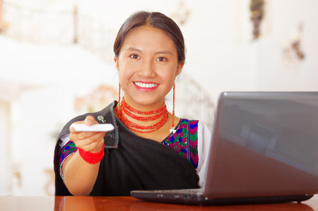 hotel receptionist: Young brunette wearing traditional native clothes working as hotel receptionist with friendly smile handing over key to client across desk, customers point of view.