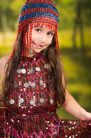 Cute little girl wearing beautiful red dress with matching pearl hat, posing for camera, green forest background. Stock Photo