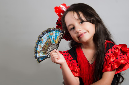 dance preteen: Cute little girl wearing beautiful red and black dress with matching head band, posing for camera using chinese hand fan, studio background.