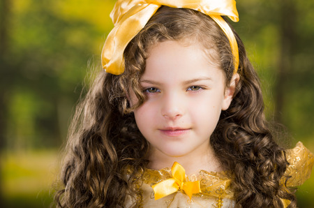 dance preteen: Headshot cute little girl wearing beautiful yellow dress with matching head band, posing for camera, green forest background.