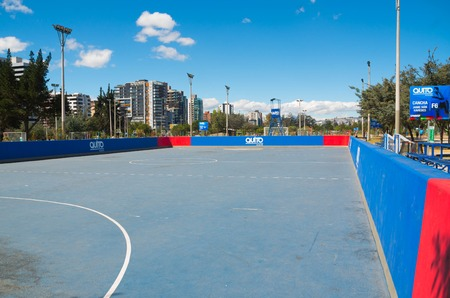 inner city: QUITO, ECUADOR - 8 AUGUST, 2016: Blue surfaced land hockey field with walls sourrounding, located in inner city park La Carolina, beautiful sunny day.