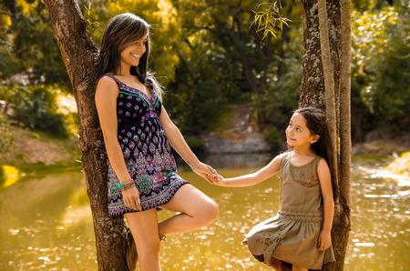 Mother with little daughter dressed in summerly dresses posing happily holding hands for camera, outdoor small forest lake background.
