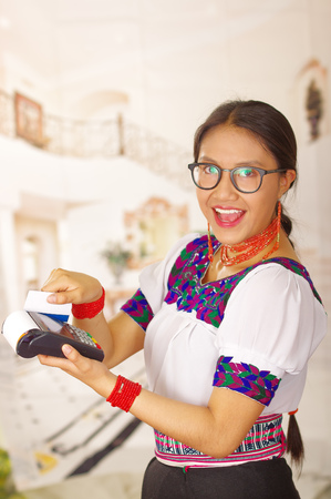 Young brunette wearing traditional native clothes working as hotel receptionist with friendly smile, processing payment using credit card terminal, customers point of view.