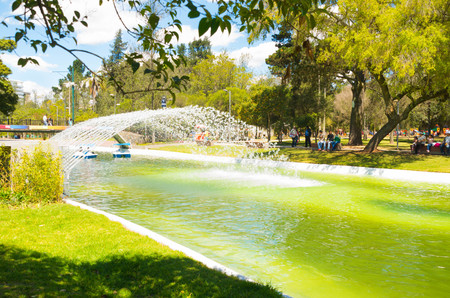 inner city: Peaceful laguna inside inner city park, water arch shooting across channel on a beautiful sunny day. Stock Photo