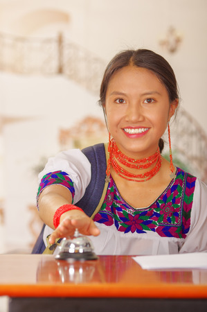 hotel receptionist: Young brunette wearing traditional native clothes working as hotel receptionist with friendly smile pressing desk bell, customers point of view.