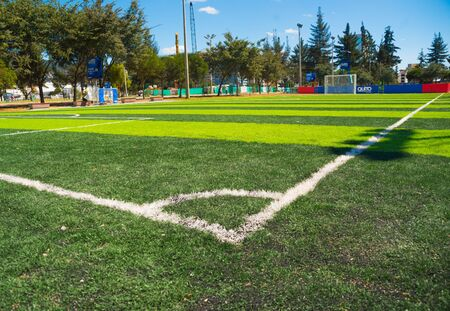 inner city: QUITO, ECUADOR - 8 AUGUST, 2016: Great perspective of artificial grass football field located in inner city park La Carolina, taken from corner flag showing trees and buildings, beautiful sunny day. Stock Photo