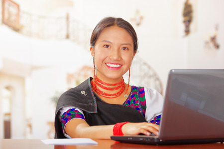 hotel receptionist: Young brunette wearing traditional native clothes working as hotel receptionist with friendly smile, using computer, customers point of view. Stock Photo