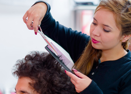 hairstylists: Hairstylists cutting a man curly hair, she is using a comb and scissors.