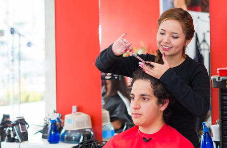 hairstylists: Inside a barbershop a young and nice hairstylists is cutting the hair of a man with curly hair.