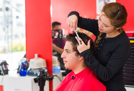 hairstylist: Latin man with curly hair inside a barber shop, nice hairstylist with scissors is cutting his hair.