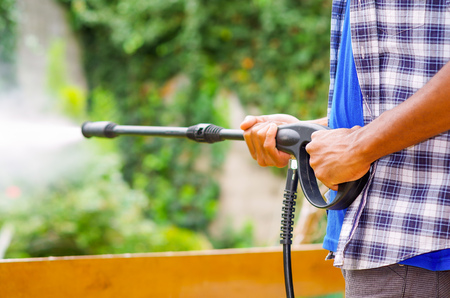 pressured: Closeup arms of man wearing square pattern blue and white shirt holding high pressure water gun, pointing towards green garden. Stock Photo