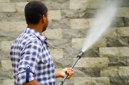 pressured: Man wearing square pattern blue and white shirt holding high pressure water gun, pointing towards grey brick wall. Stock Photo