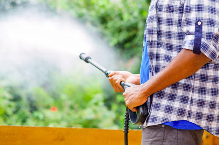 Closeup arms of man wearing square pattern blue and white shirt holding high pressure water gun, pointing towards green garden. Stock Photo