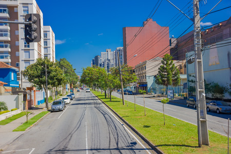 autos: CURITIBA ,BRAZIL - MAY 12, 2016: long empty street with some autos parked at the sides and some trees on the sidewalk.