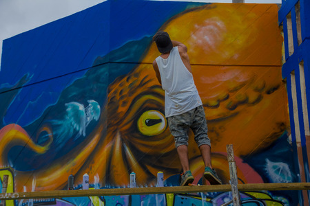 grafitti: PUNTA DEL ESTE, URUGUAY - MAY 06, 2016: young man finishing a grafitti painted in the wall. Editorial