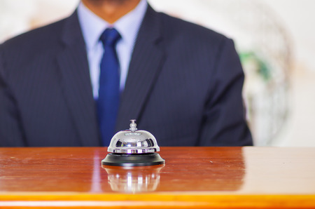 standing reception: Elegant blue business suit standing behind desk bell at hotel reception. Stock Photo