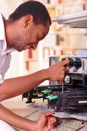 fotocopiadora: Man leaning over open photocopier during maintenance repairs using handheld tool, black mechanical parts.