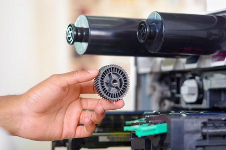 fotocopiadora: primer plano la mano delante de la fotocopiadora abierta durante las reparaciones de mantenimiento utilizando la herramienta de mano, piezas mecánicas negro.