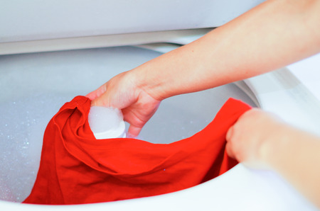 Closeup womans hands putting red clothing into washing machine, laundry housework concept.