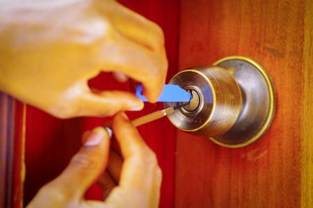 Close-up handen van de slotenmaker met behulp van metalen pick tools waarmee vergrendelde deur te openen.