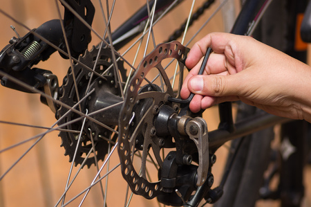shifting: Closeup detailed look at bicycle wheel gear shifting mechanics during maintenance repairs, hand using tool working.